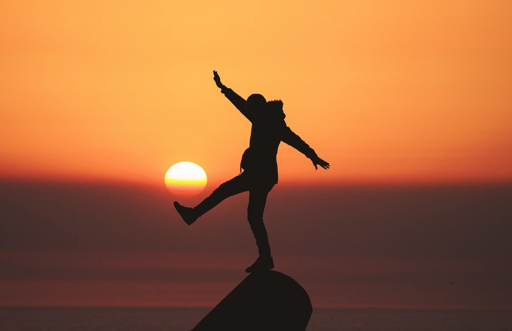 A silhouette of a figure stands on a rock in front of an orange sunset. They have their arms out to the side and one leg raised as they balance on the rock.