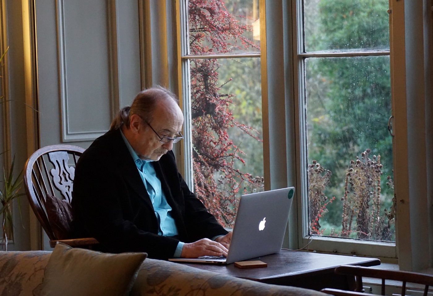 An elderly man using a Macbook