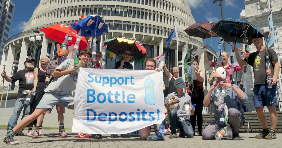 Kiwi Bottle Drive campaigns stand outside the Beehive with a banner that says, Support Bottle Deposits. Many of them are hold