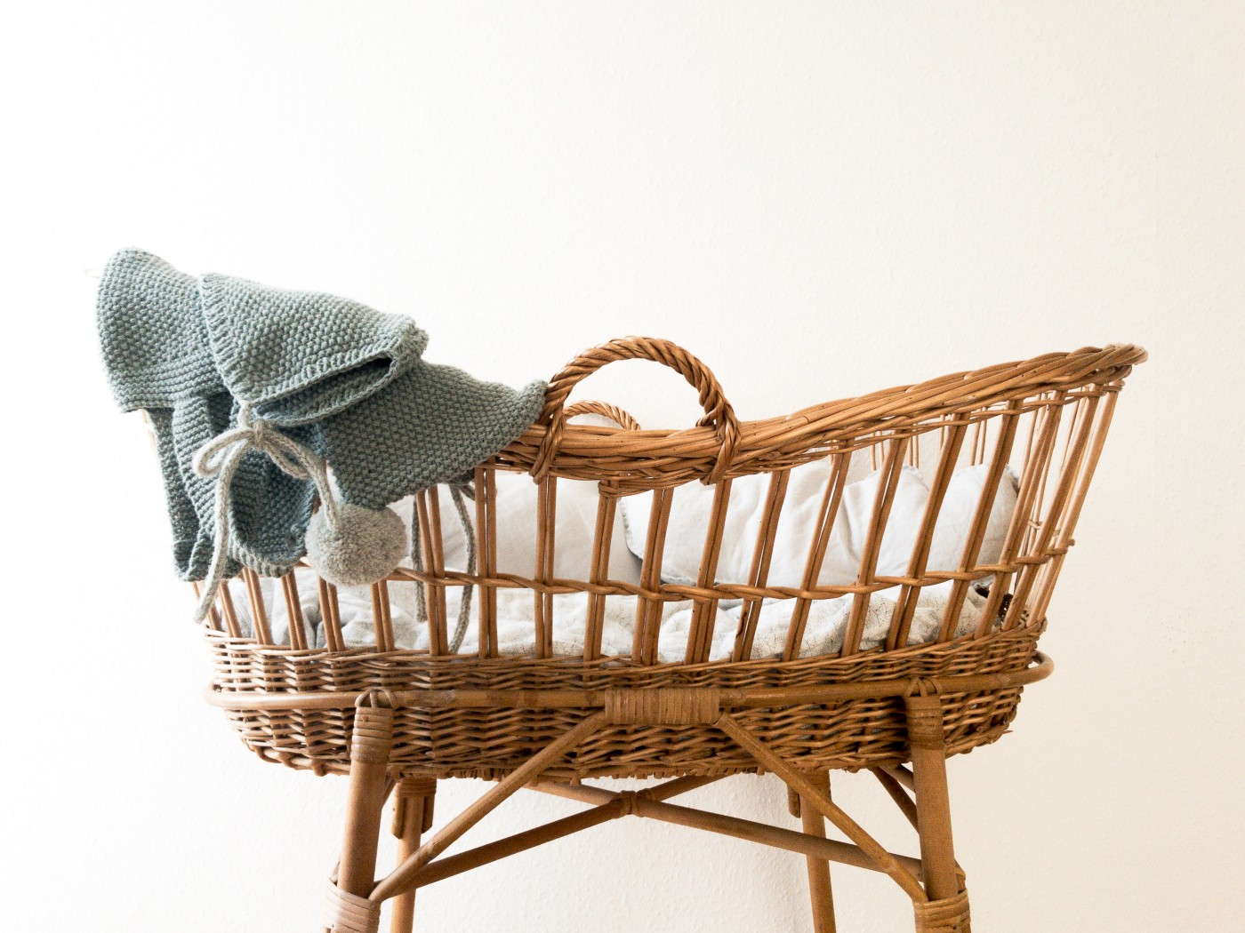 straw bassonet for a baby with a blue blanket