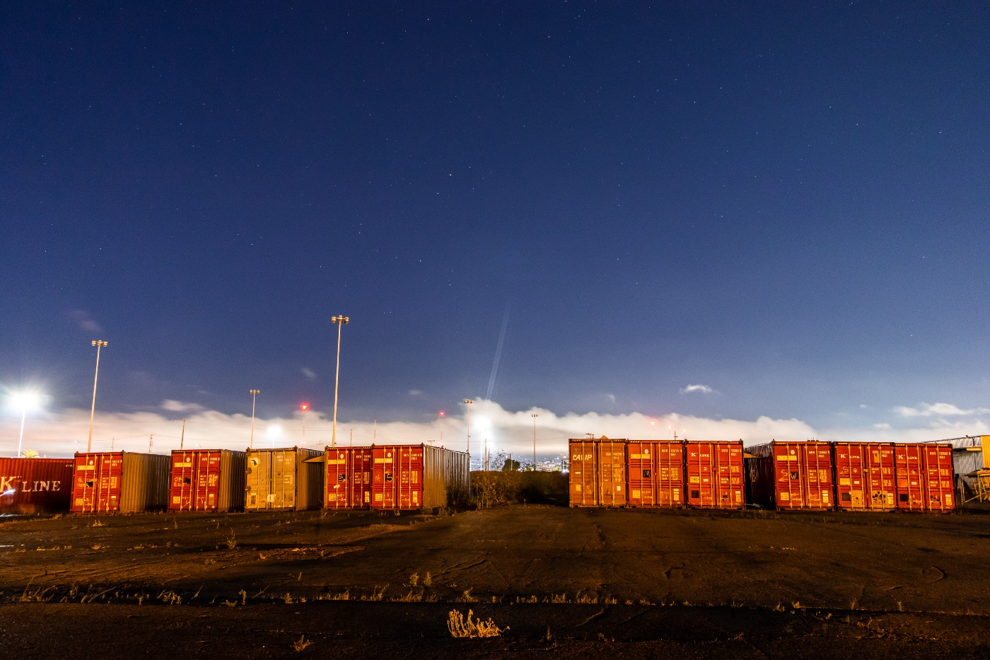 A set of containers with a skyline in the background.