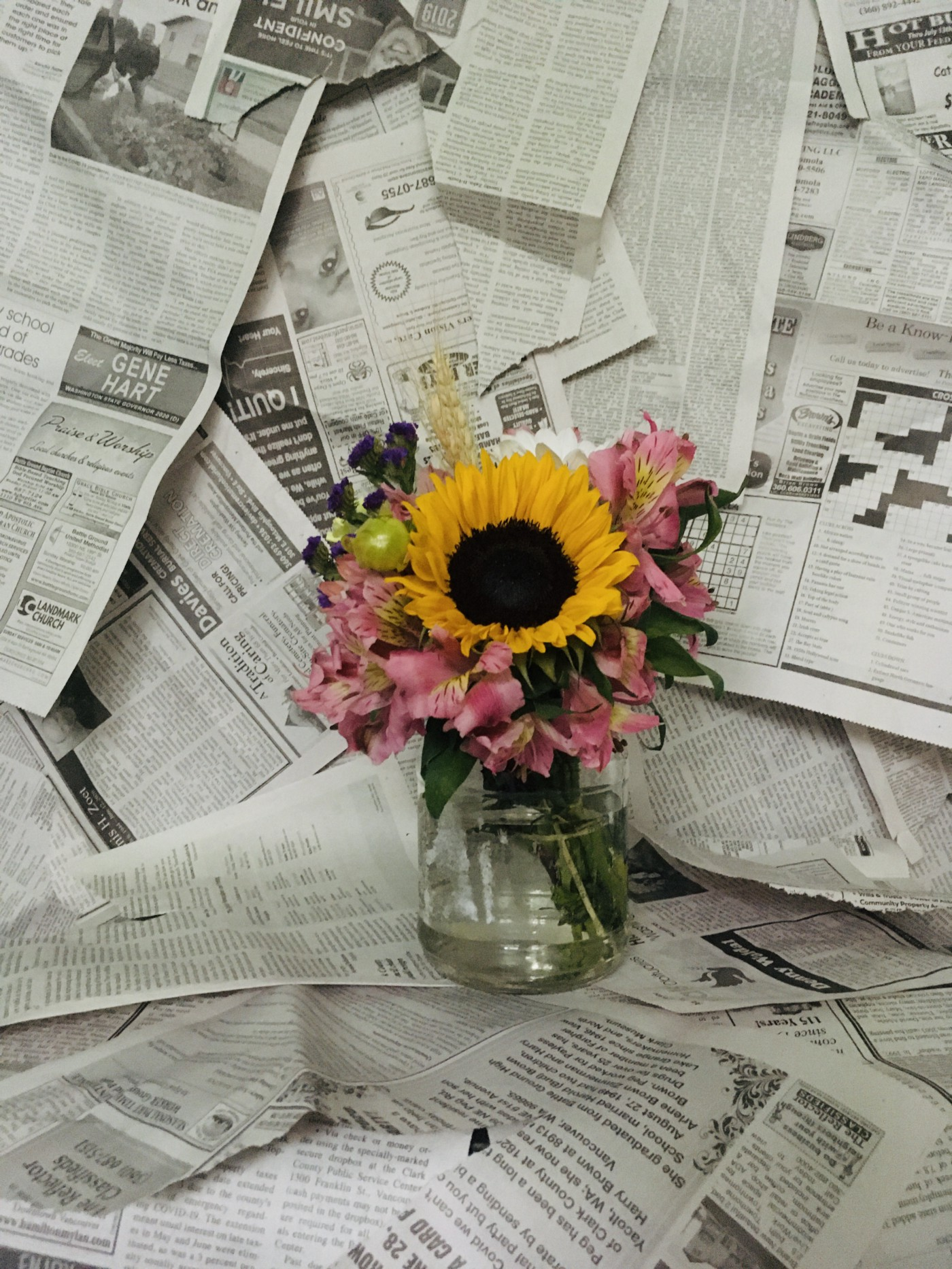 Newspaper clippings with a bouquet set on them