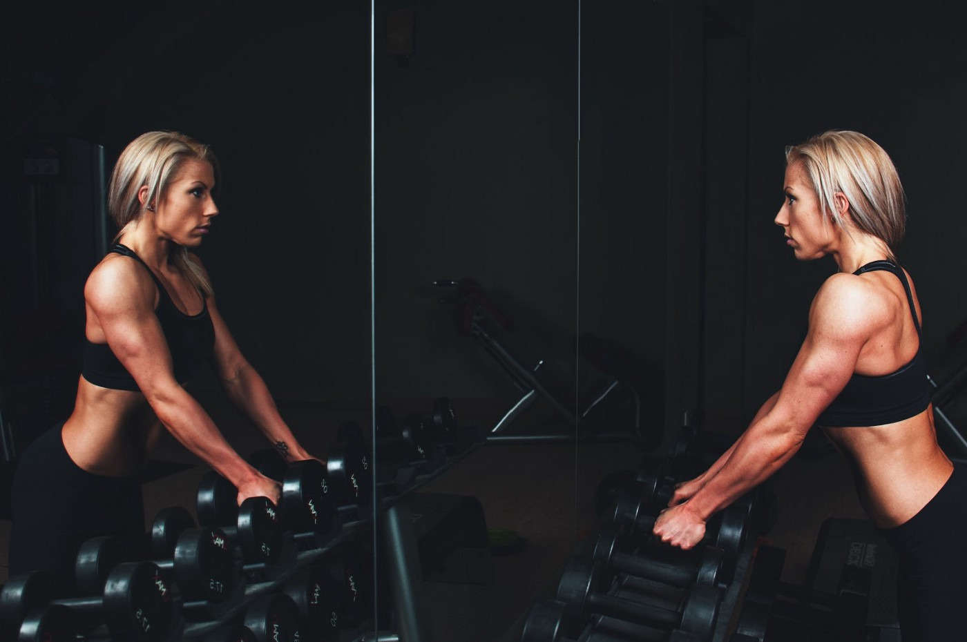 Fit blond woman holding weights and looking at herself in a gym mirror