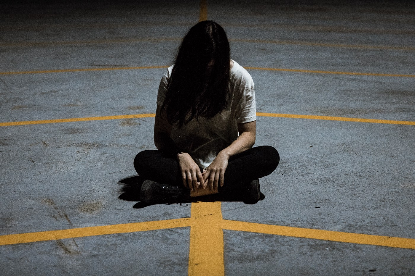 Stock photo of a woman sitting cross-legged on a concrete floor. Her hair is covering her face.