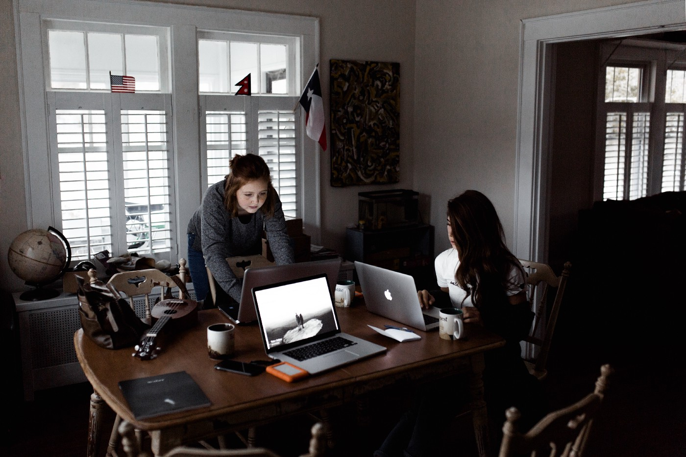 Two caucasian women are at a large wooden dining table inside a domestic home. The woman to the right of the table has long, black wavy hair and is seated while working on her silver laptop. The other woman has short brown hair and is leaning over the table on the far side of it, also working on her laptop. There is a third laptop open on the table and is not in use by anyone.