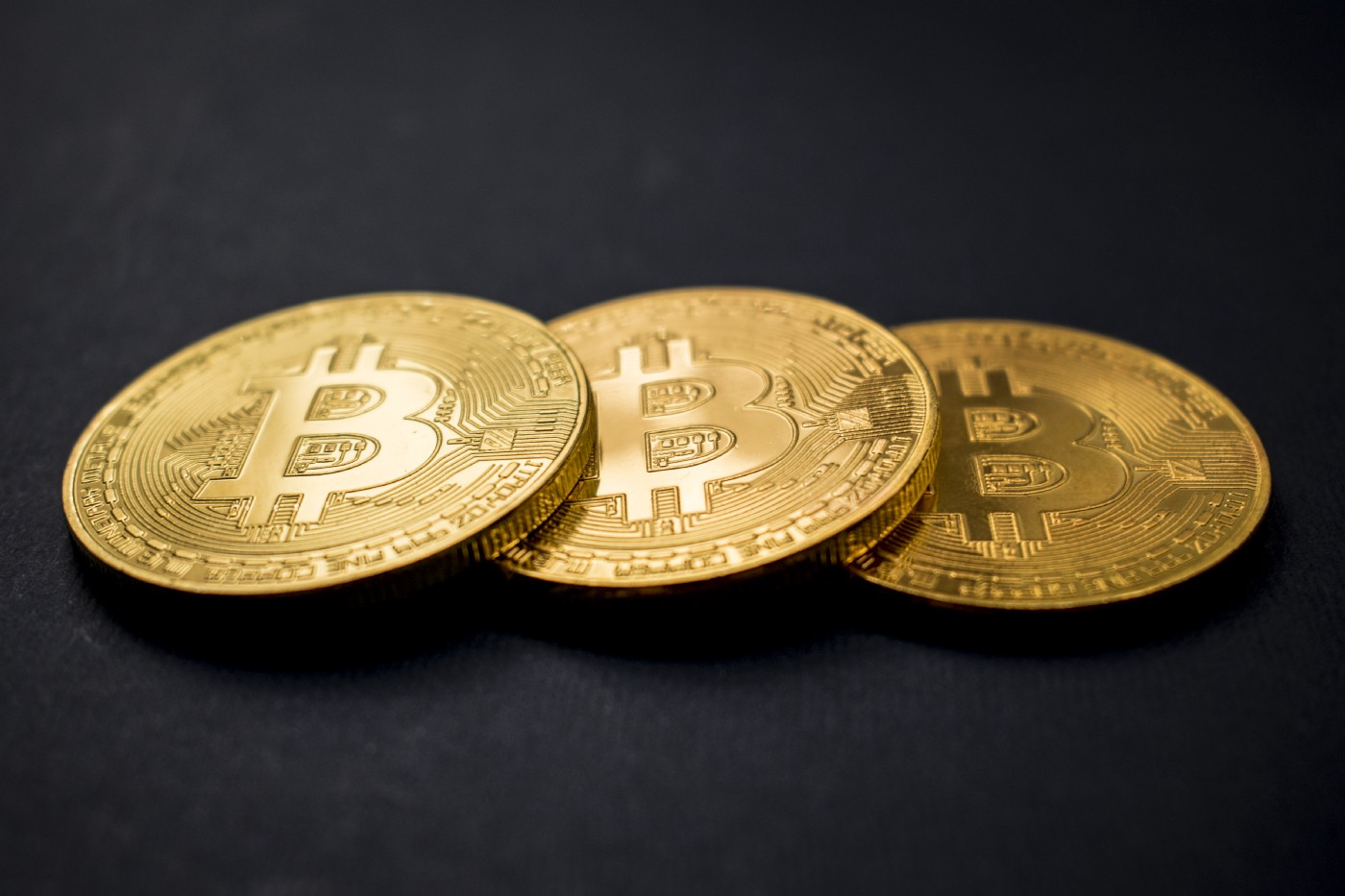 A title image with three golden Bitcoins in front of a dark background.