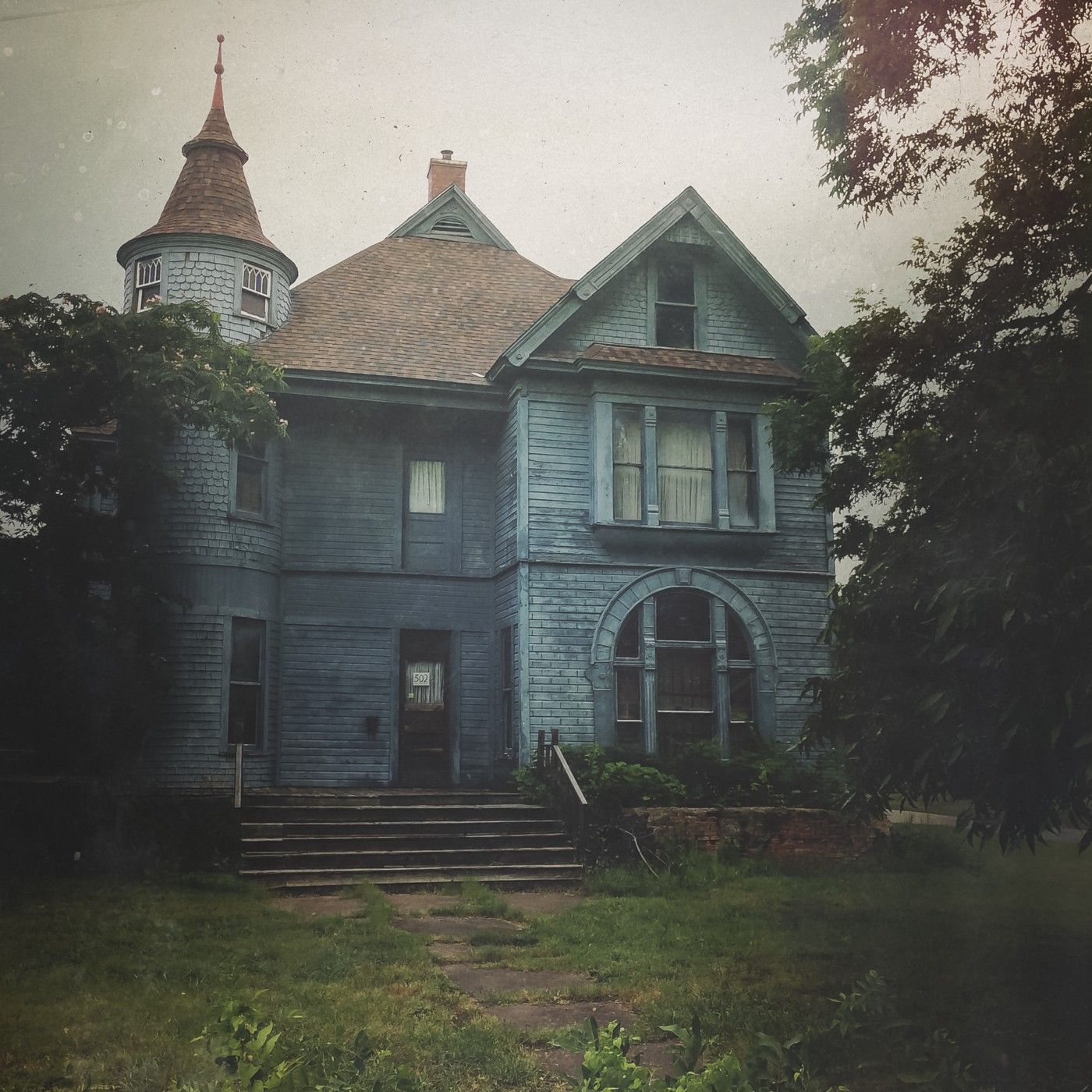 Creepy looking house with turret, steps and air of abandonment.