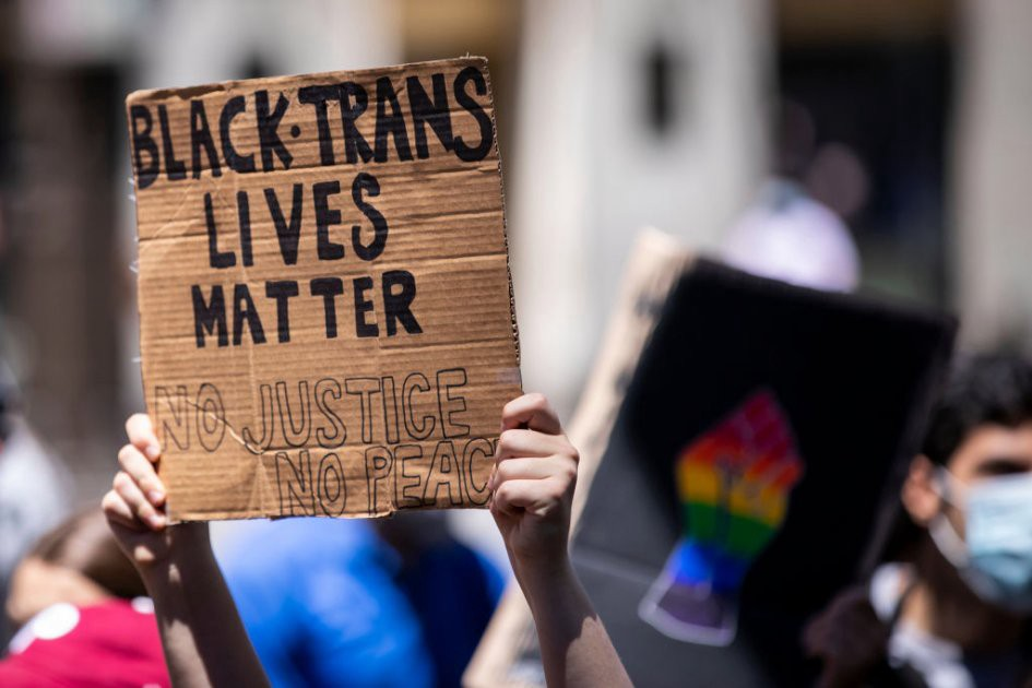 "A protester holds up their homemade sign on a box that says, ""Black Trans Lives Matter No Justice No Peace"""