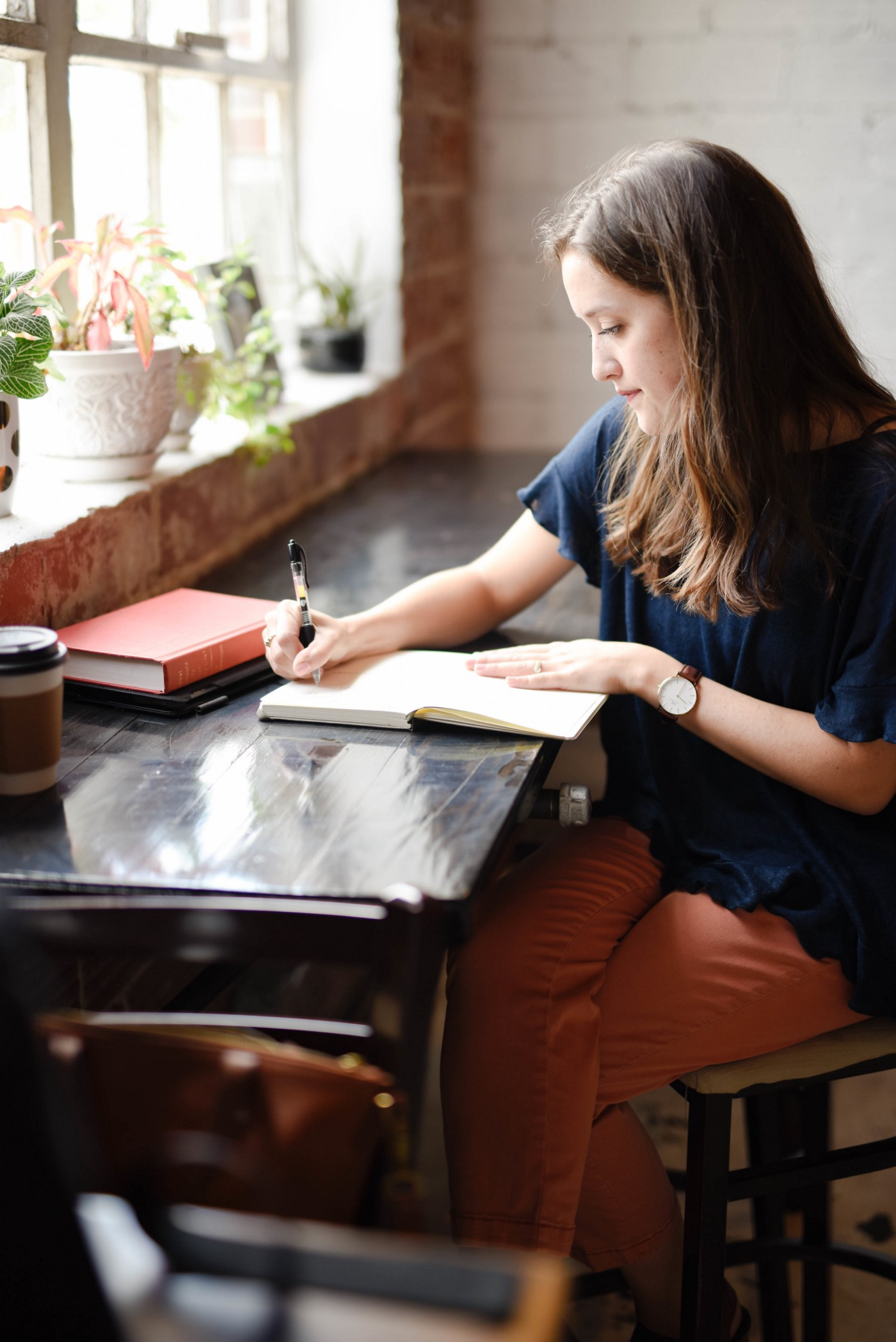 Woman sitting at a coffee shop with a notebook open and a pen in her hand.