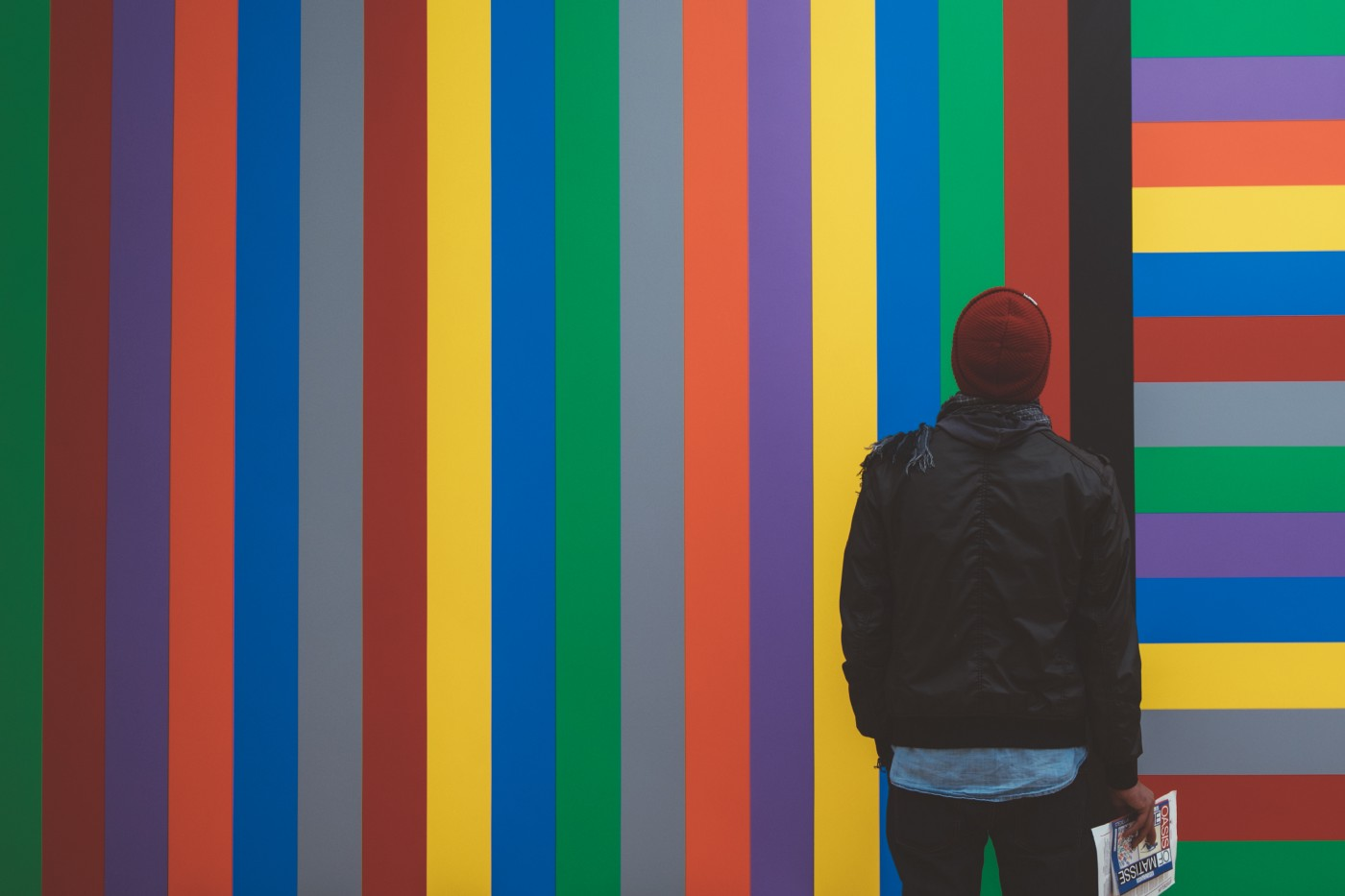 A man holding a newspaper stares at a wall painted with brightly colored vertical stripes