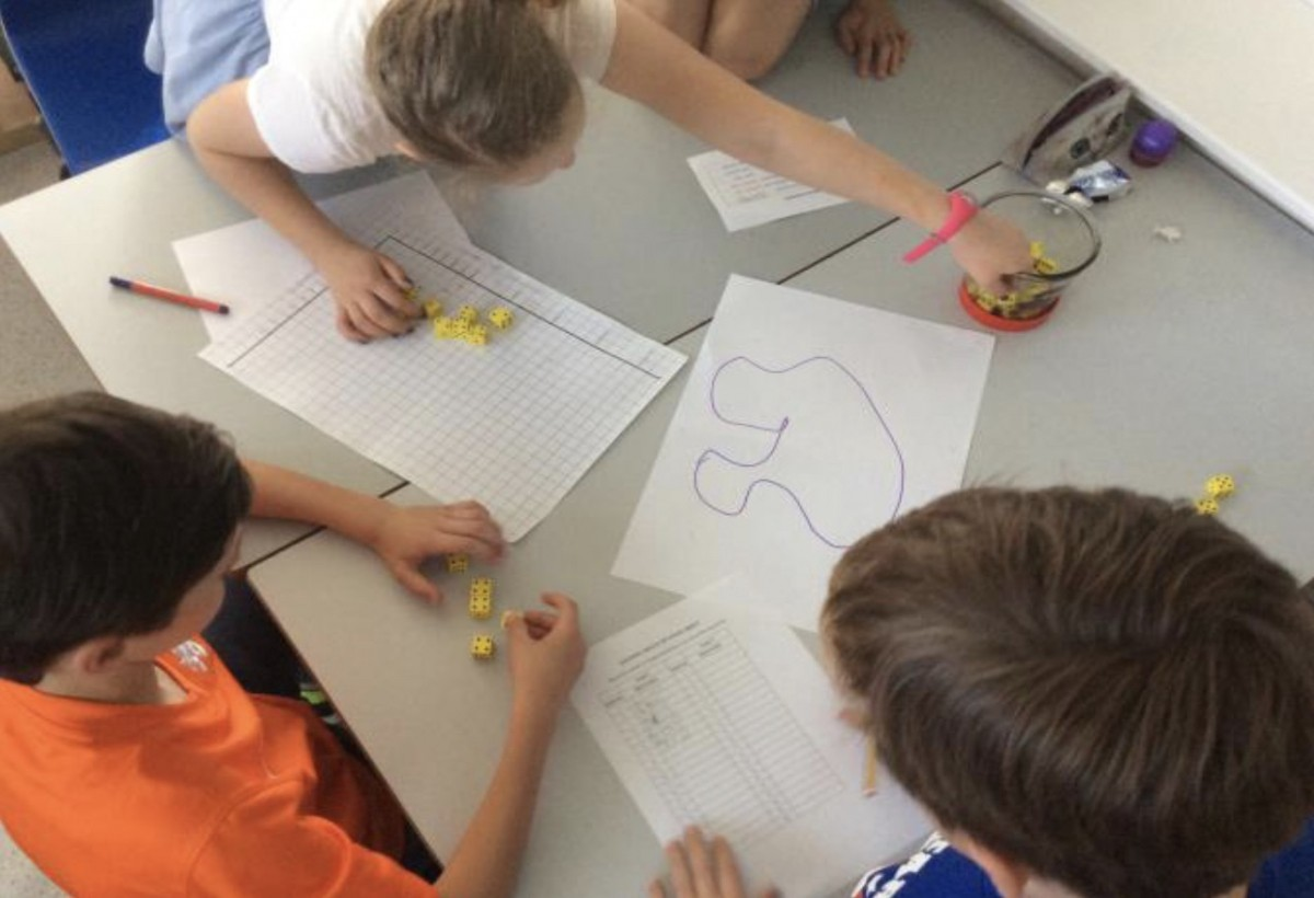 Children graphing out data points at a school work table
