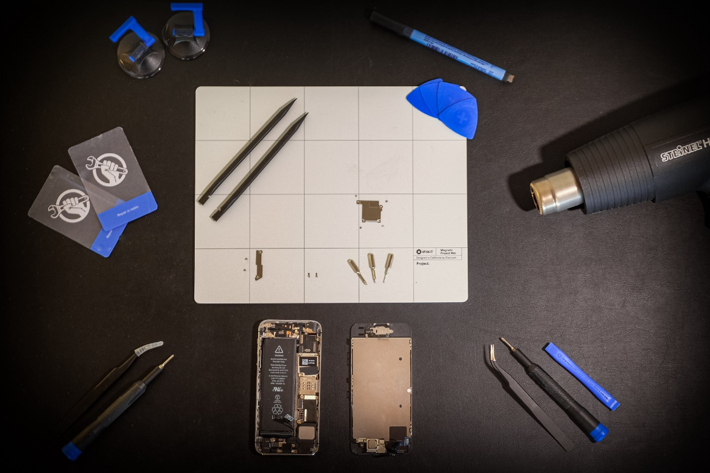 A disassembled smartphone and several tools sitting on a table