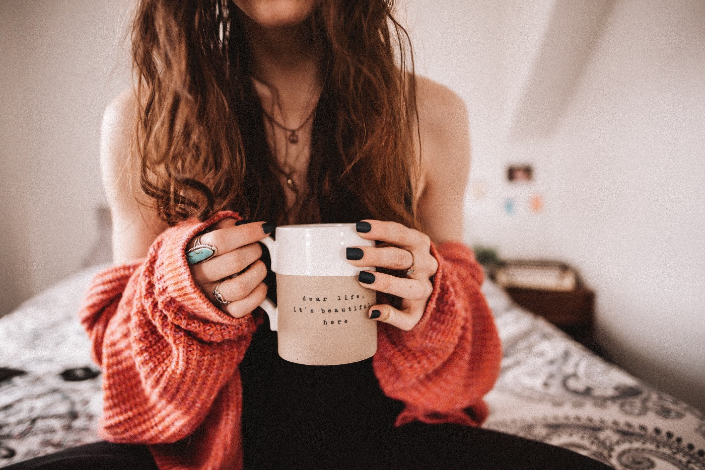 "A person sits on a bed while holding a coffee cup that reads ""dear life, it's beautiful here."""
