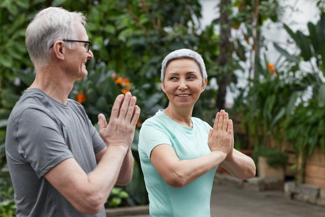 Senior couple in short sleeved shirts standing next to each other in a yoga pose with their hands together as in prayer.