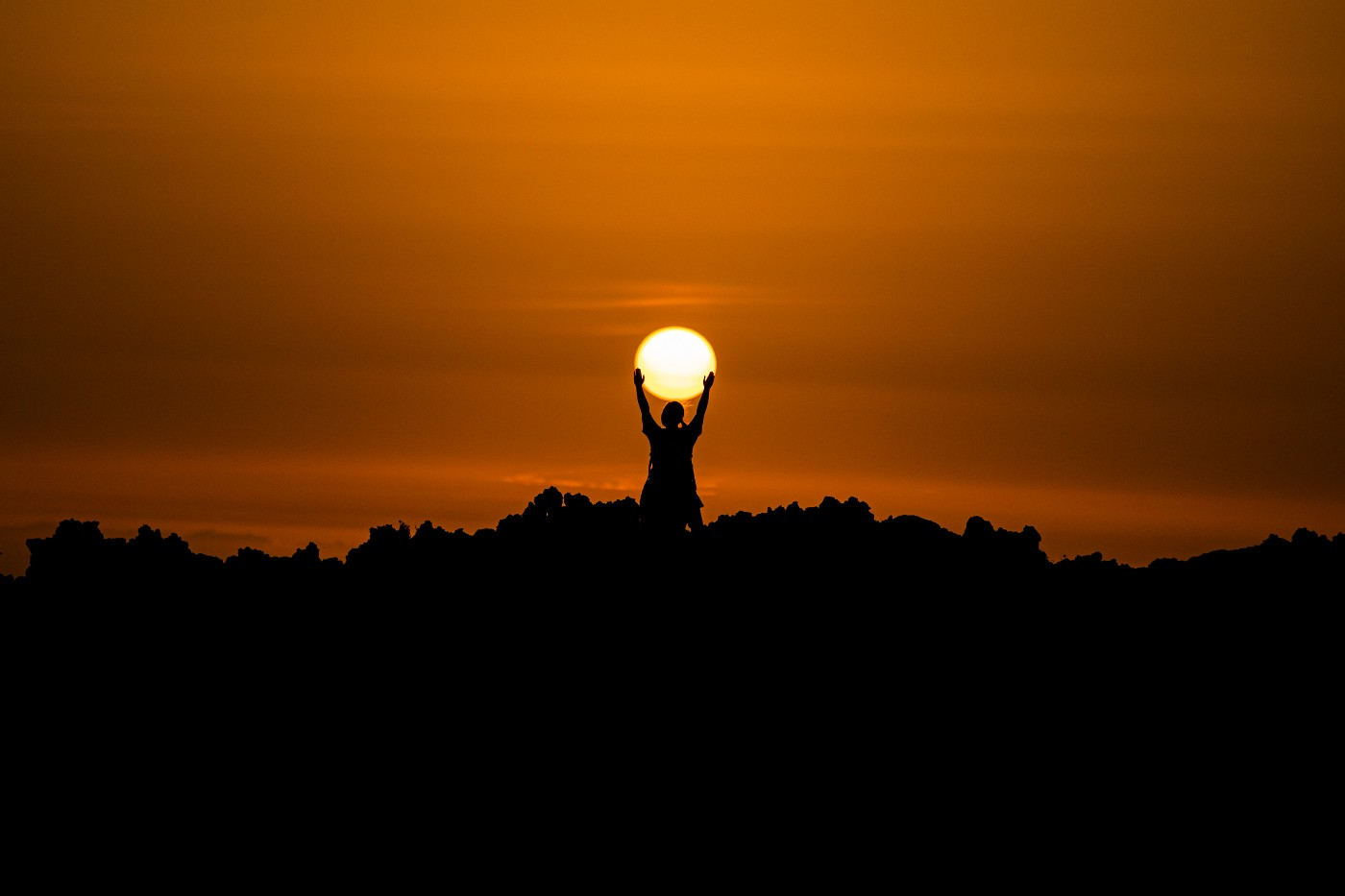"""Image of person """"holding"""" the sun."""