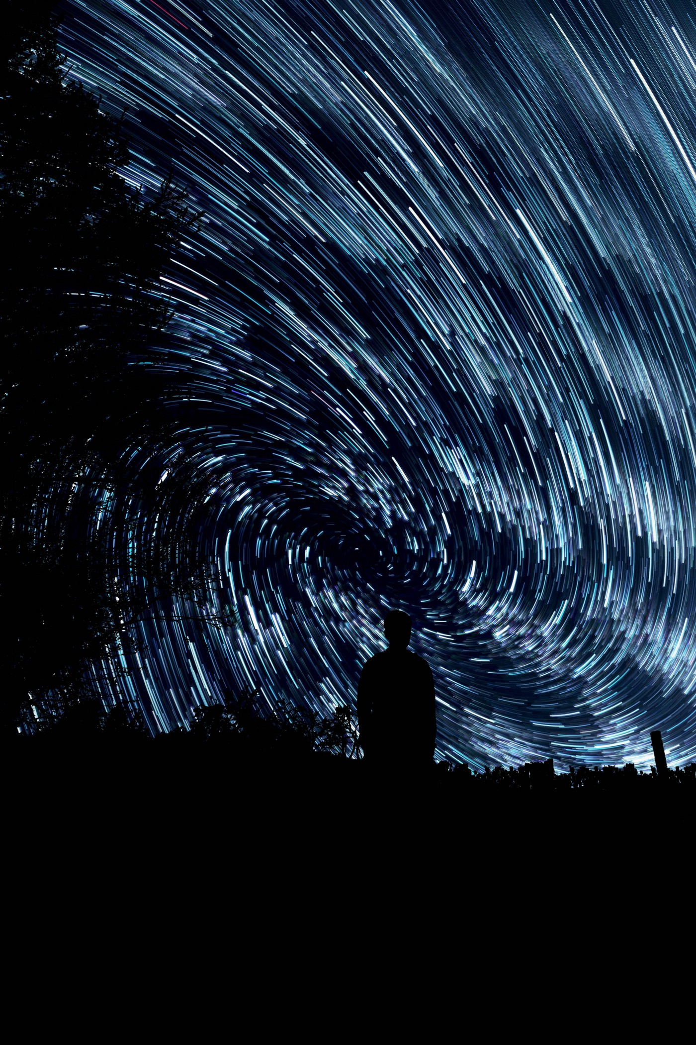 Night sky with star trails and silhouetted figure.