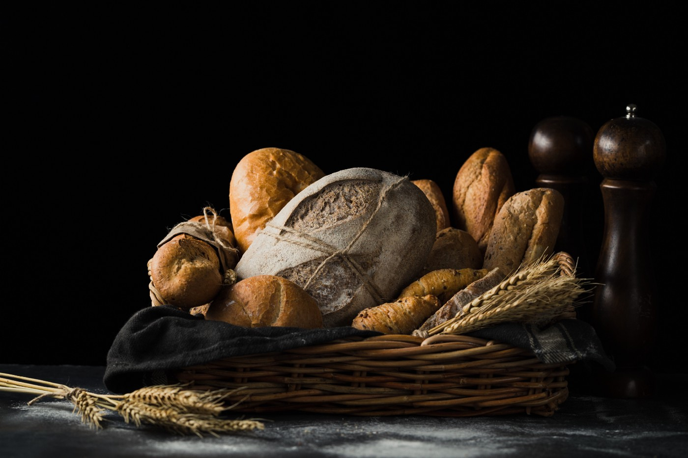 A basket of bread, stalks of wheat, and salt and pepper shakers against a black background