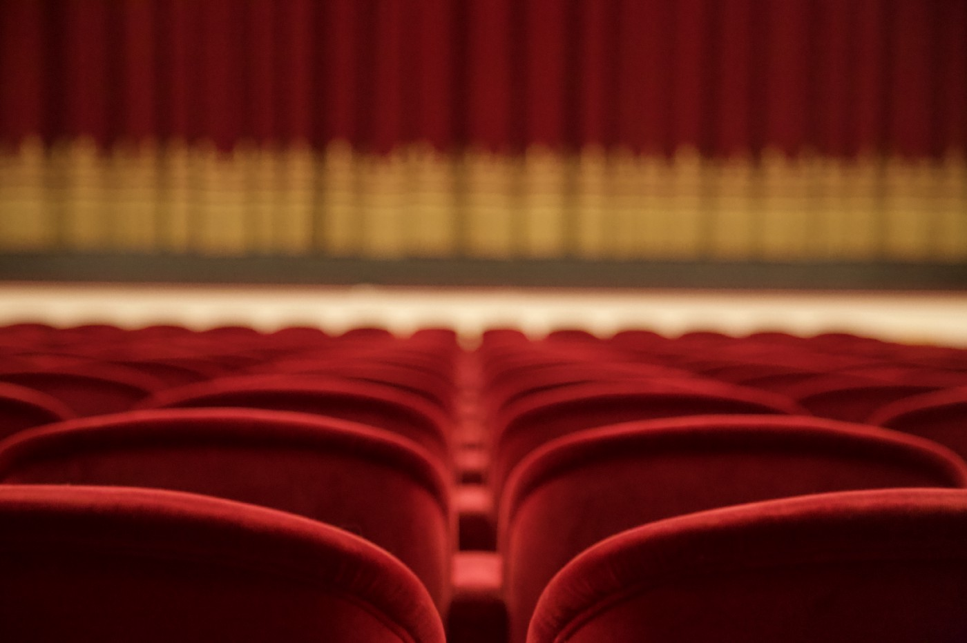 A theater. Perspective from the audience. Rows of empty red velvet chairs and in the distance, a red curtain with gold trim.