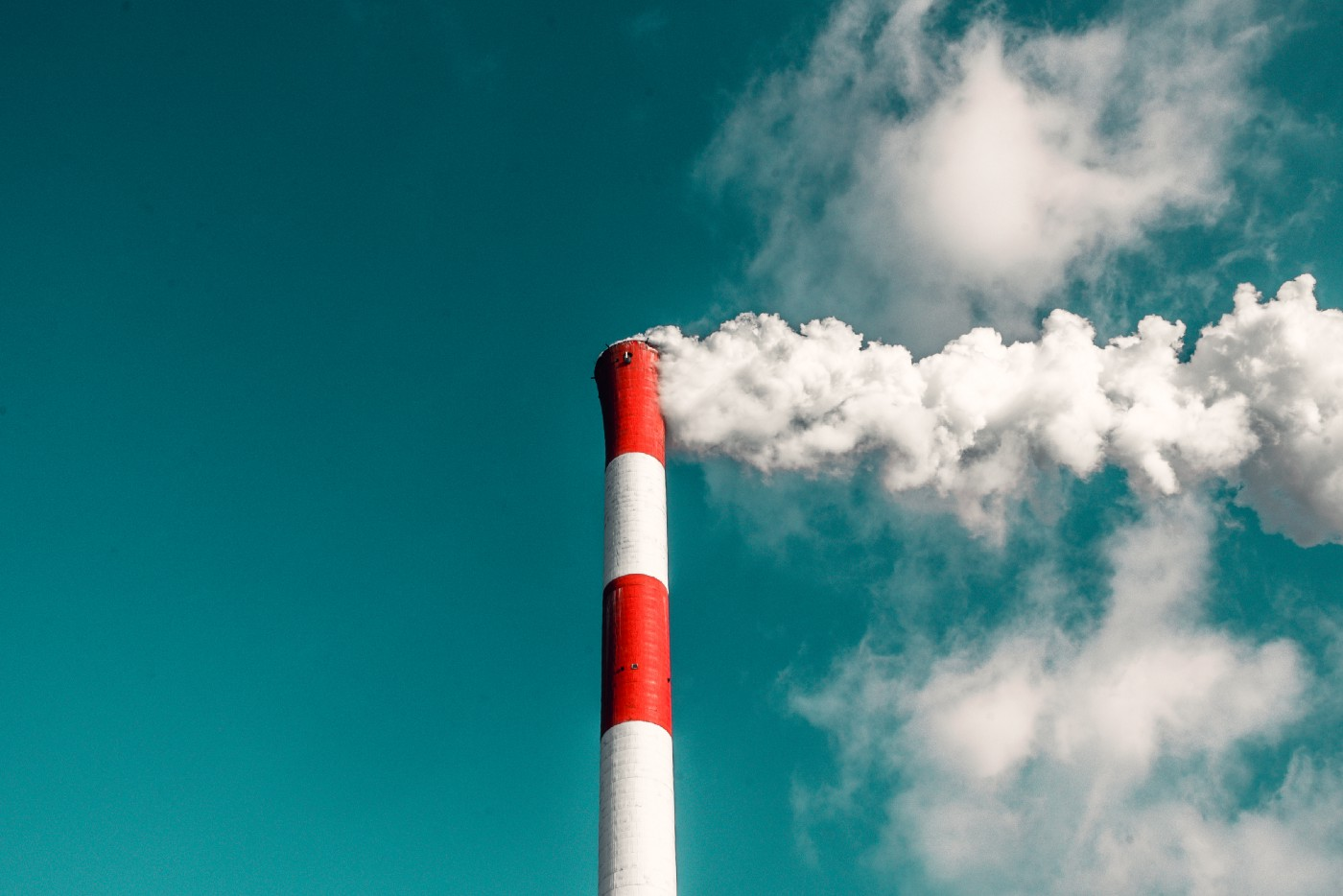 Image of an industrial chimney polluting the clear blue sky with its smoke.