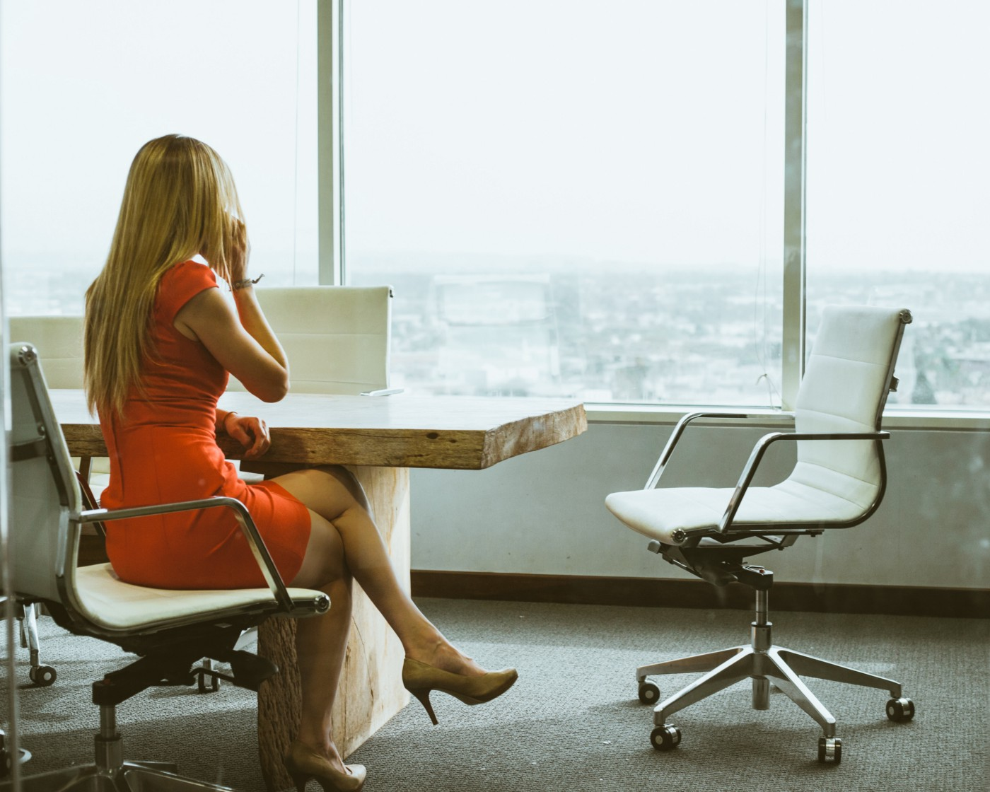 Blond woman sitting at a conference table using a cell phone. Large glass windows showing the view from a high-rise beyond.