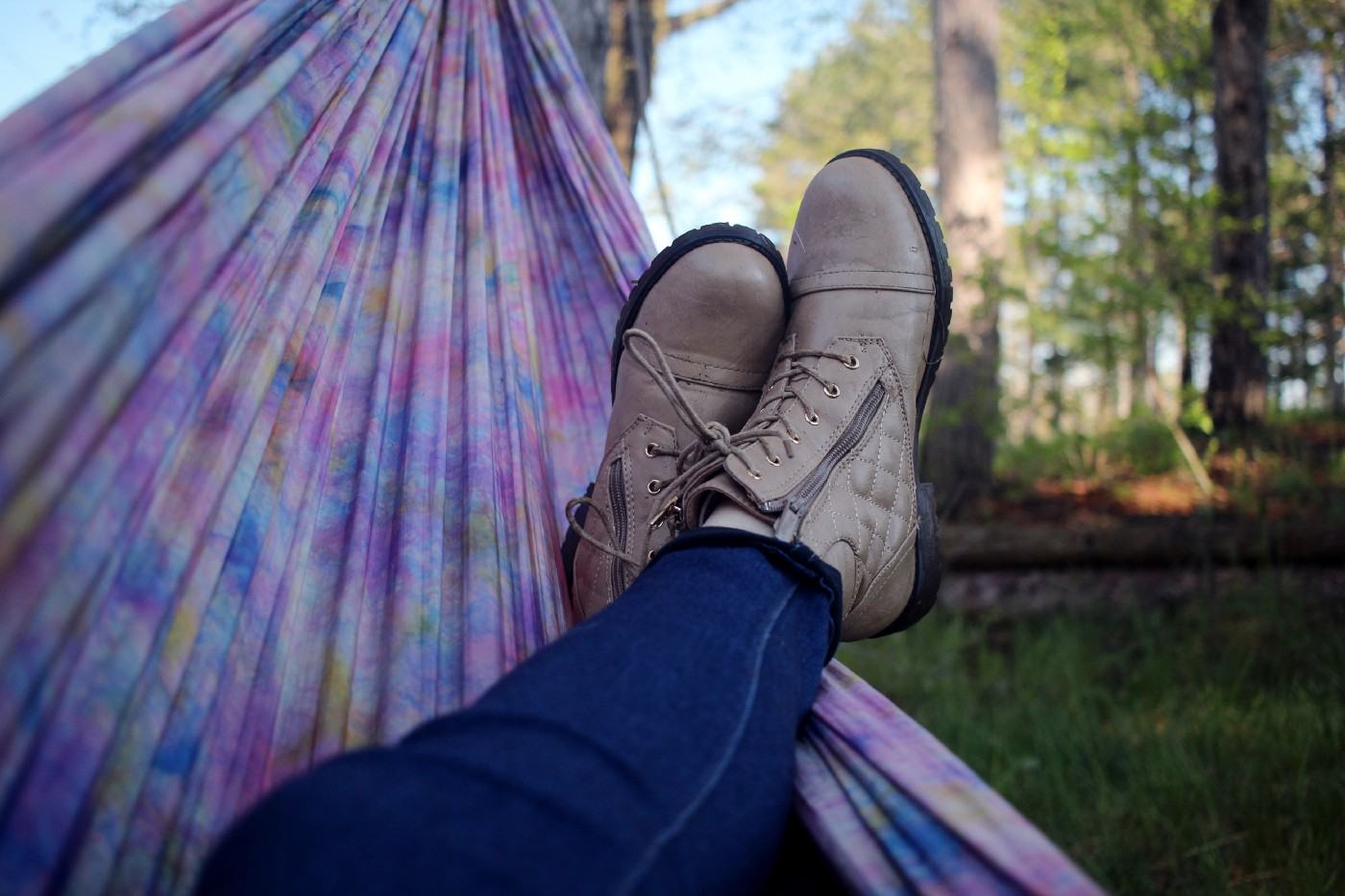 Picture of a person relaxing on an outdoor hammock with their feet crossed.