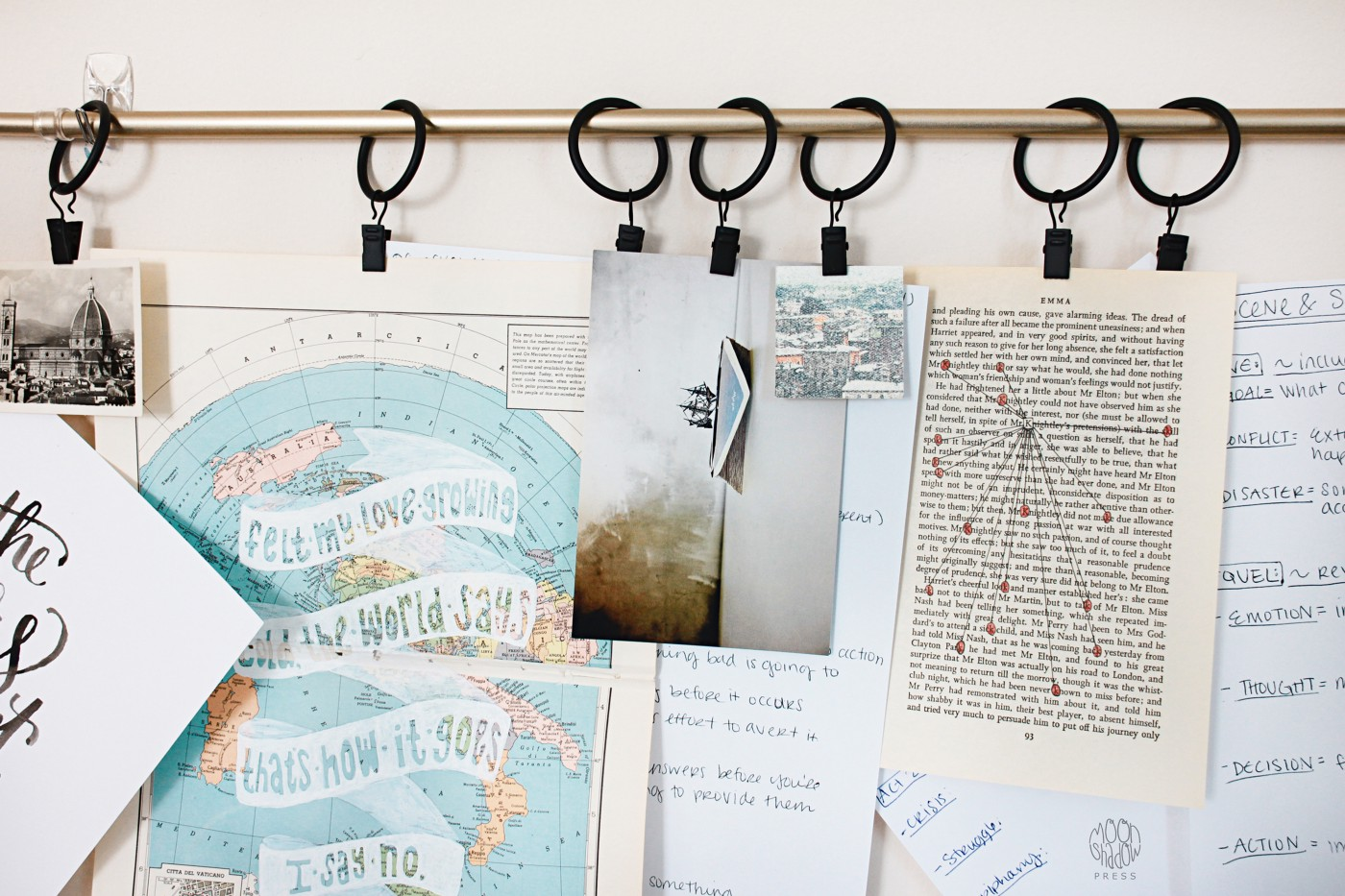 An arrangement of artwork, book pages, and postcards hanging on a wall.