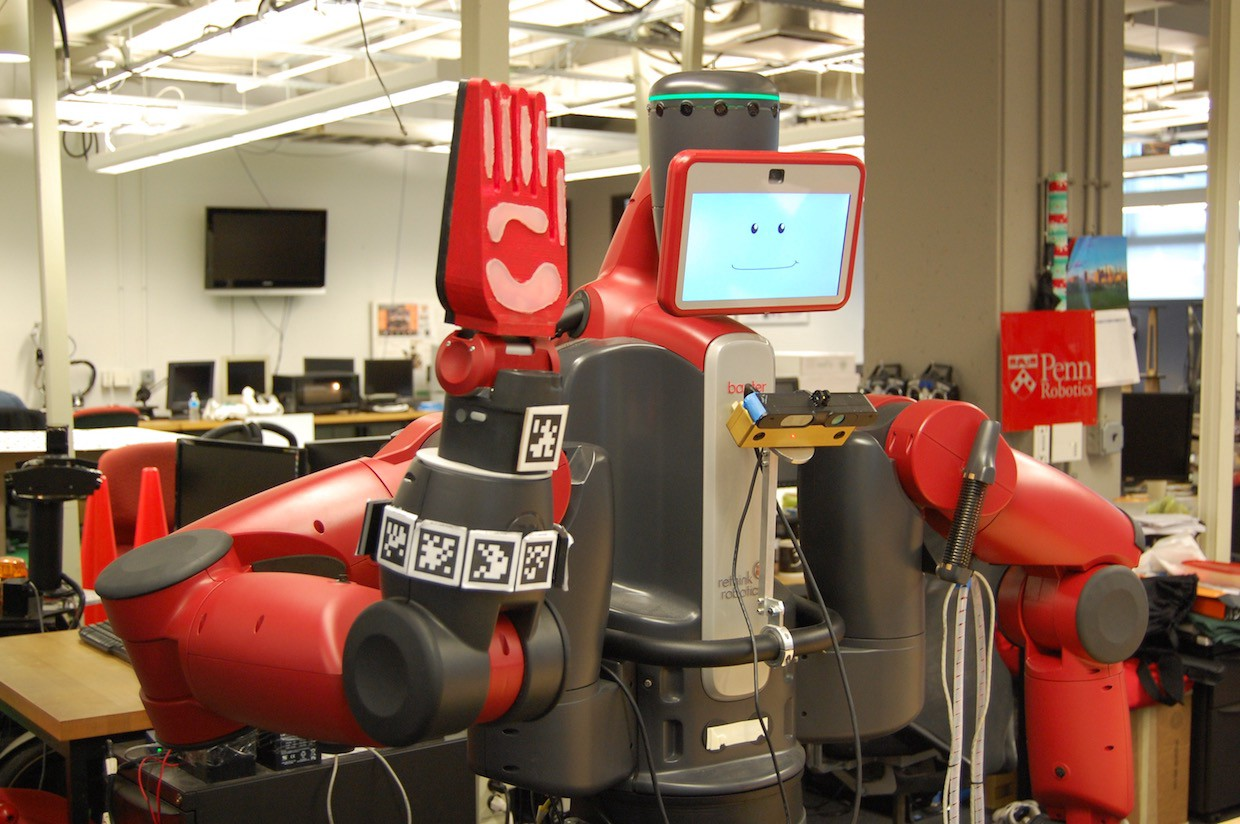 A red humanoid robot holds up its hand for a high-five. A smile is displayed on the screen that serves as its face.