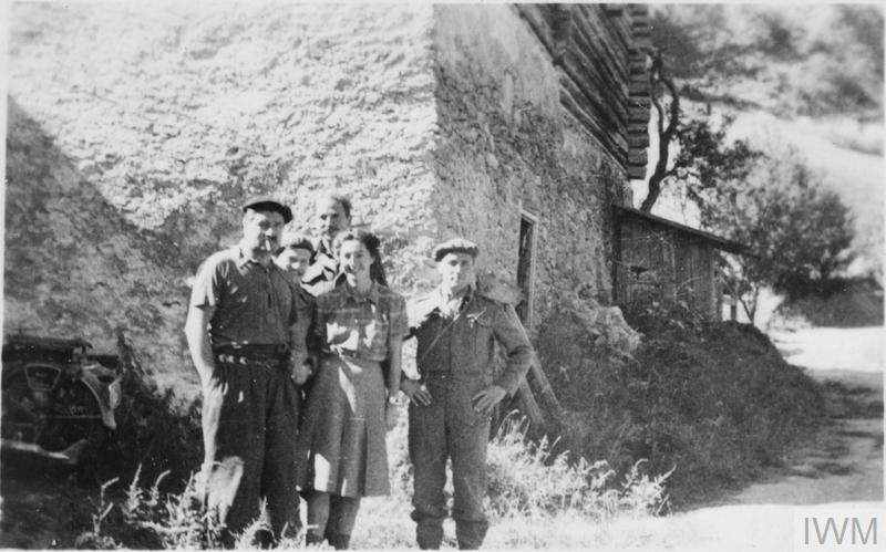 Image of five people in France. The dark-haired woman in a blouse and skirt in front is Christine Granville