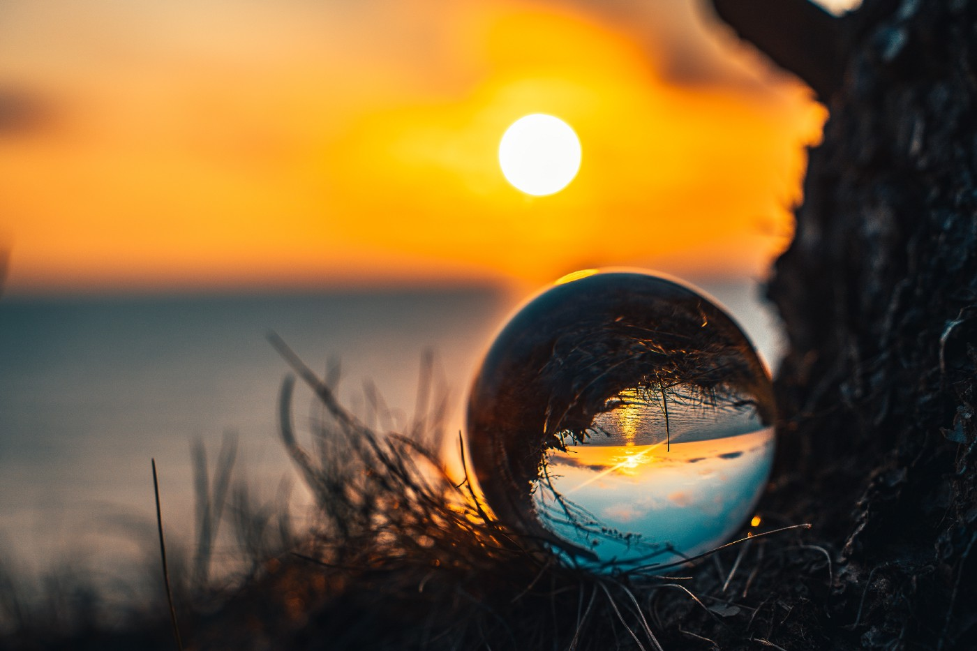 A sunrise over the ocean on a beach with a drop of water reflecting the same