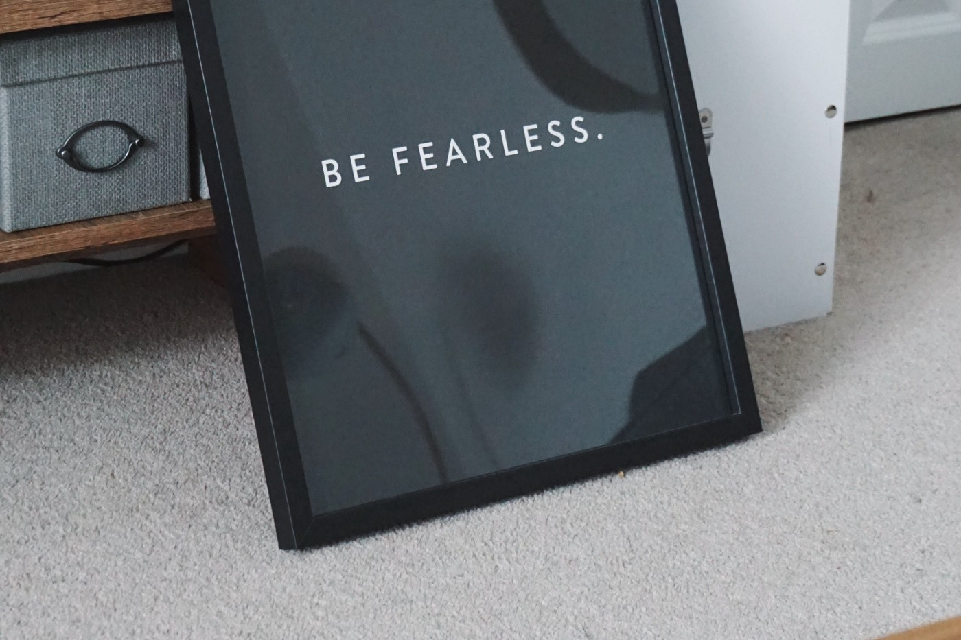 """Text """"be fearless"""" in a black photo frame."""