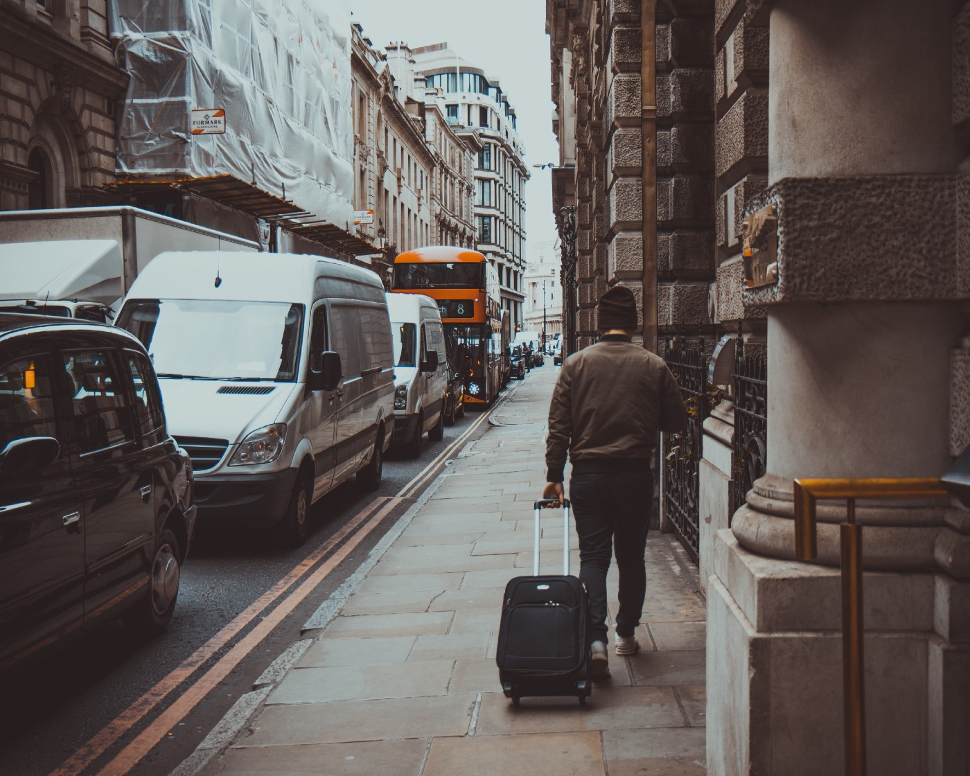Person pulling a black carry-on suitcase while walking on the pavement in London city, United Kingdom.