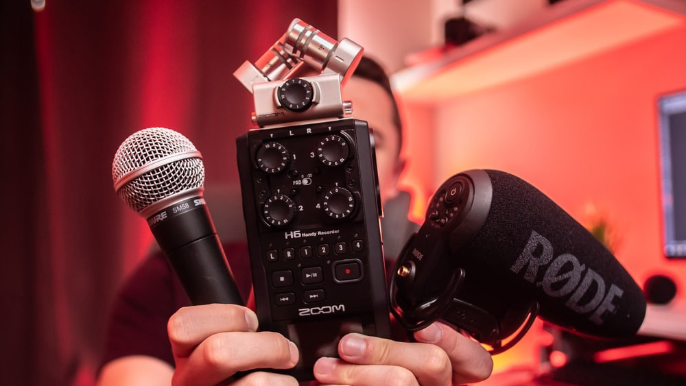 A person holds up sound equipment.