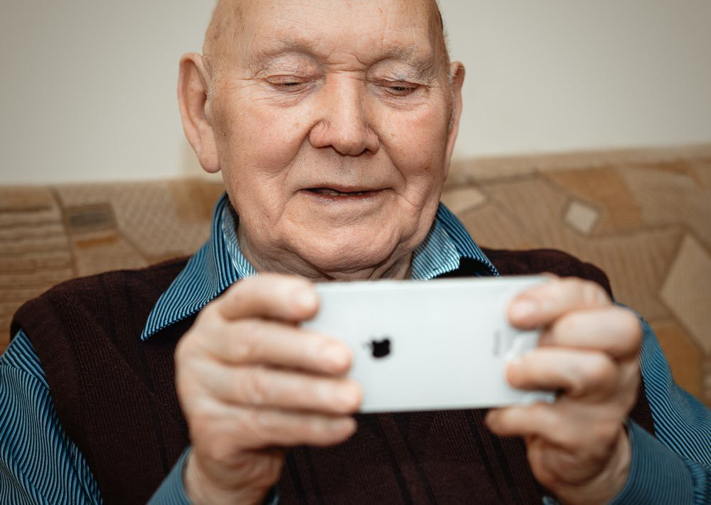 A person in their 80s using a web service on a smartphone during contextual user research.