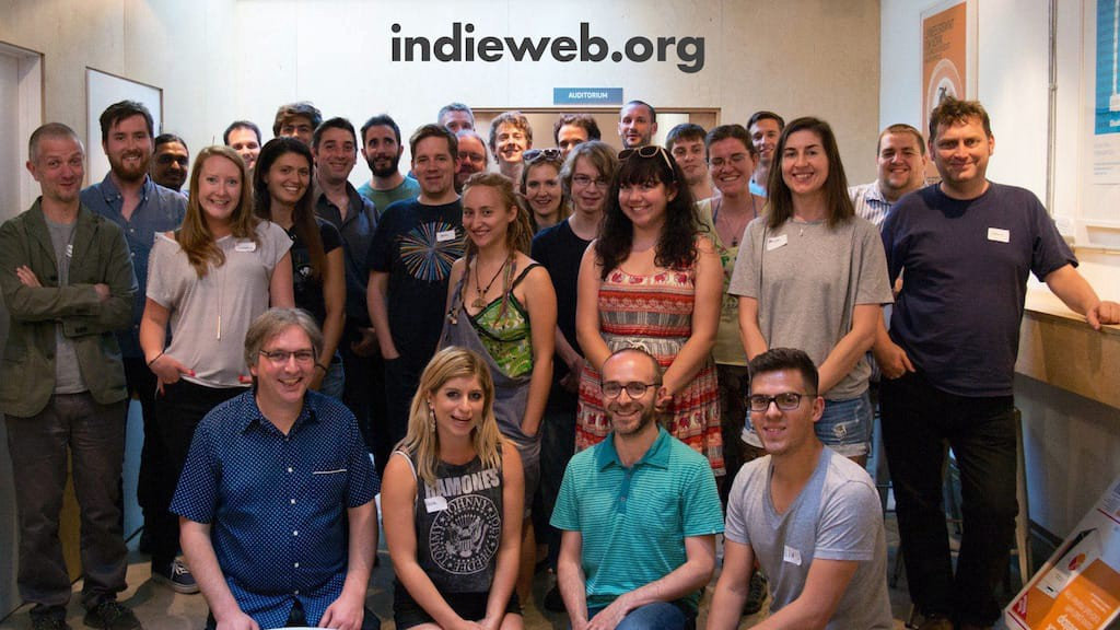 A group of smiling people, gathered together at an Indie Web Camp.