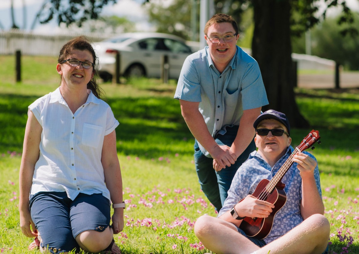Three NDIS participants sit in a park. Female on Left is wearing a white shirt and Dark pants, she has Dark Brown Hair and Glasses. Two males are on the right- one crouches down and has short Dark hair, wearing Glasses and a light shirt with Blue jeans. The other male in front wears a light blue shirt, cap, and sunglasses, and plays the ukelele.