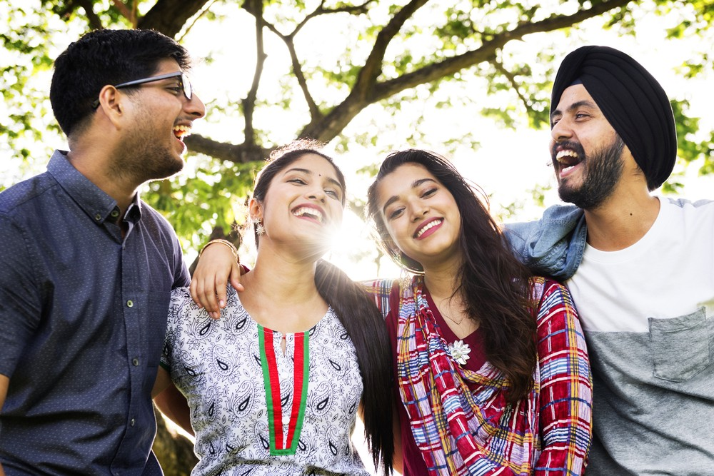 A group of friends laughing together at the park. Stress in daily life can be reduced and creativity enhanced by spending time with our loved ones.