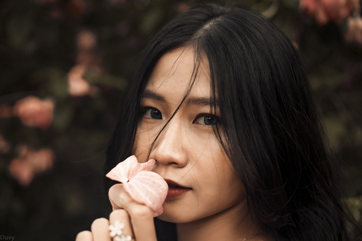 A young woman smelling flowers