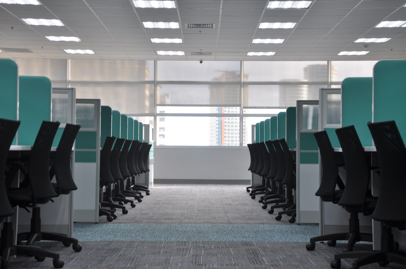 Two rows of turquoise walled cubicles with roller chairs tucked underneath. A narrow aisle leading to a window separates them.