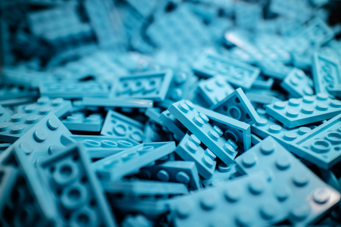 Bluewashed image of assorted Lego pieces.