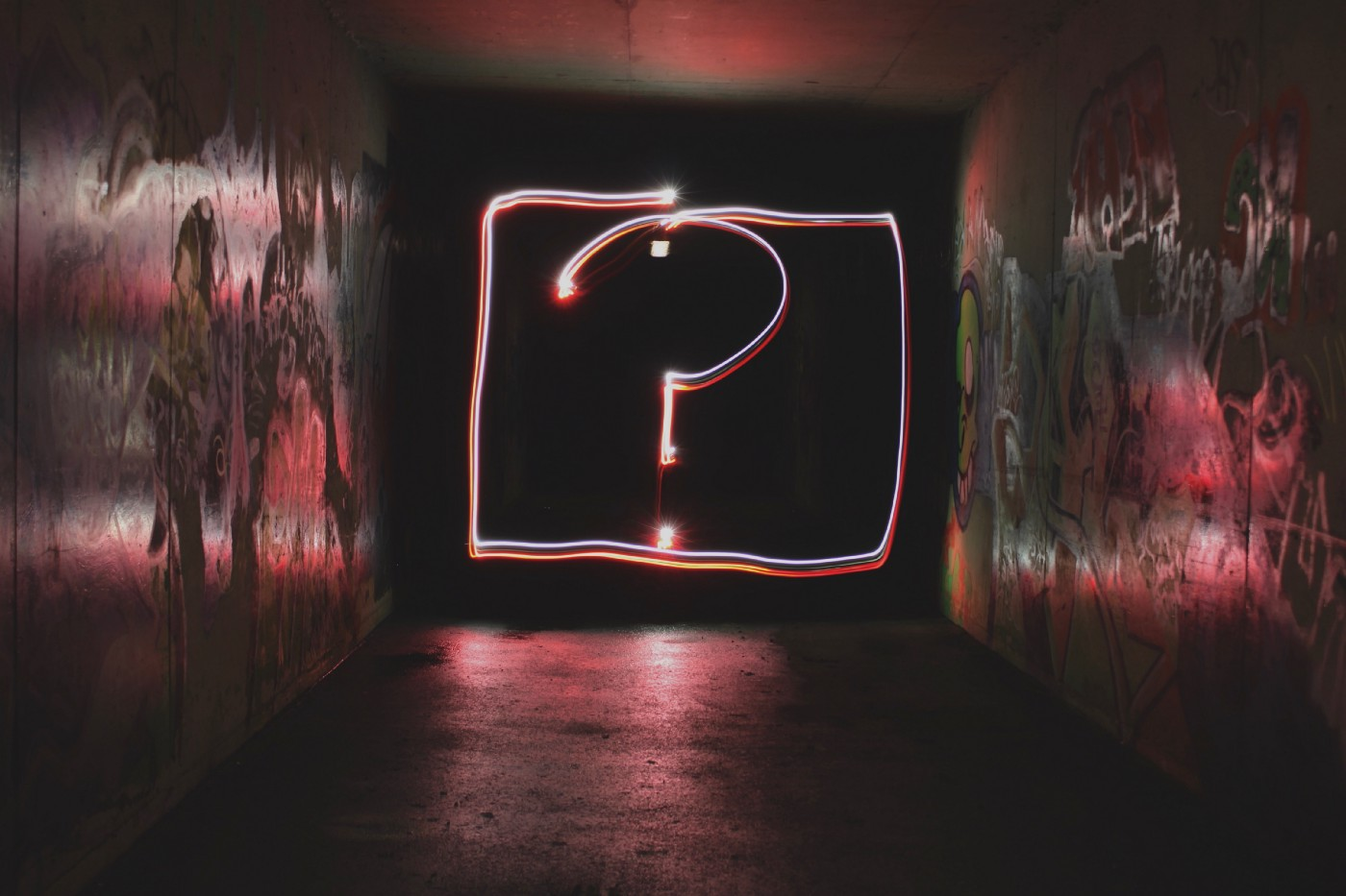 Neon question mark at the end of a dark hallway