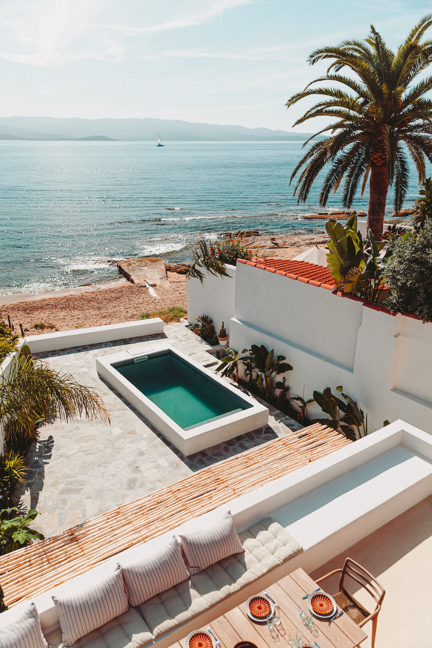The pool, surrounded by stones, palms, and white walls, sits just meters from the beach. White-painted cinder blocks and flowering trees line a stone side-pathway. (Photo: Thibaut Dini, Life's A Beach)