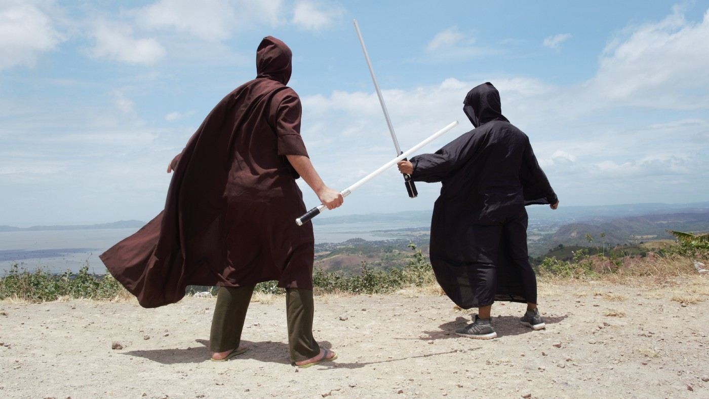 Two people duel on a hilltop