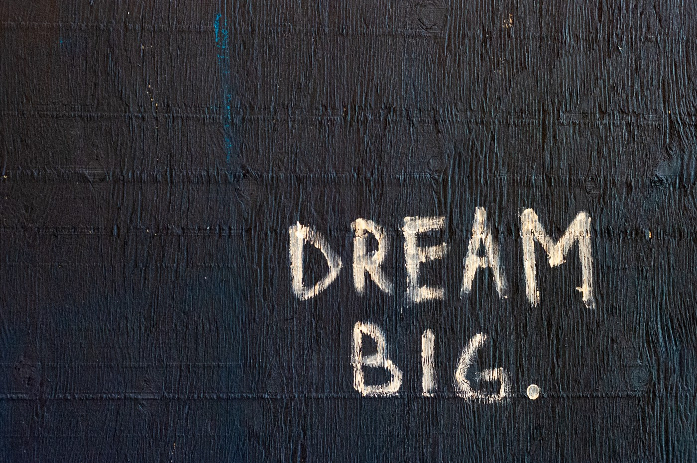 painted wooden board with scratched writing of dream big written on it