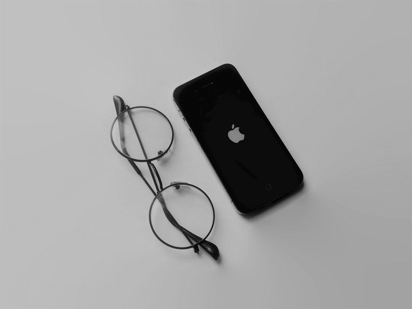 An iPhone placed next to a pair of round-framed glasses.