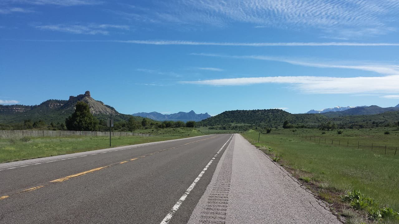 Road stretching into the distance with green hills on one side and mountains on the other