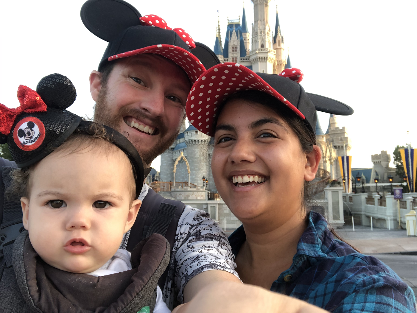Two adults and a child pose in front of Cinderella's castle in Disney World