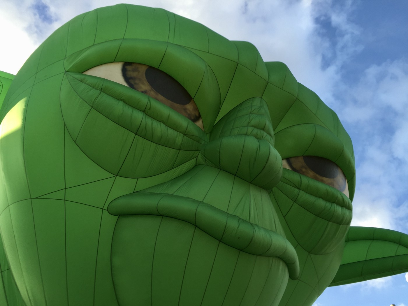 Giant green inflatable Yoda balloon peers out at the world before him.