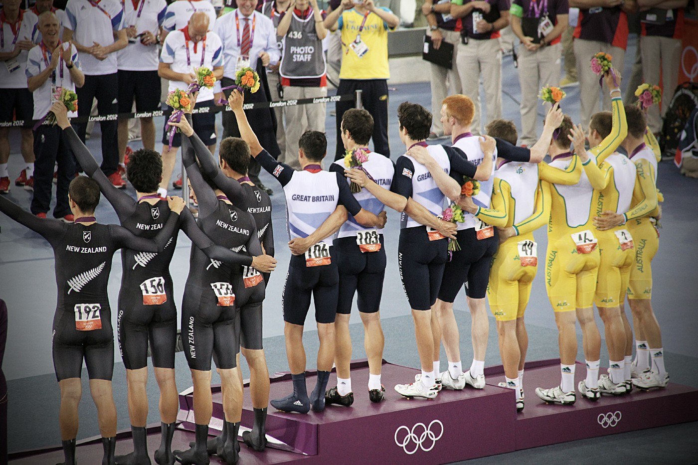 group of men standing in podium holding flowers