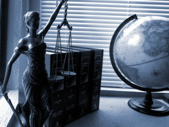 Statue of lady liberty, 4 law books, and a globe next to a window with closed mini blinds