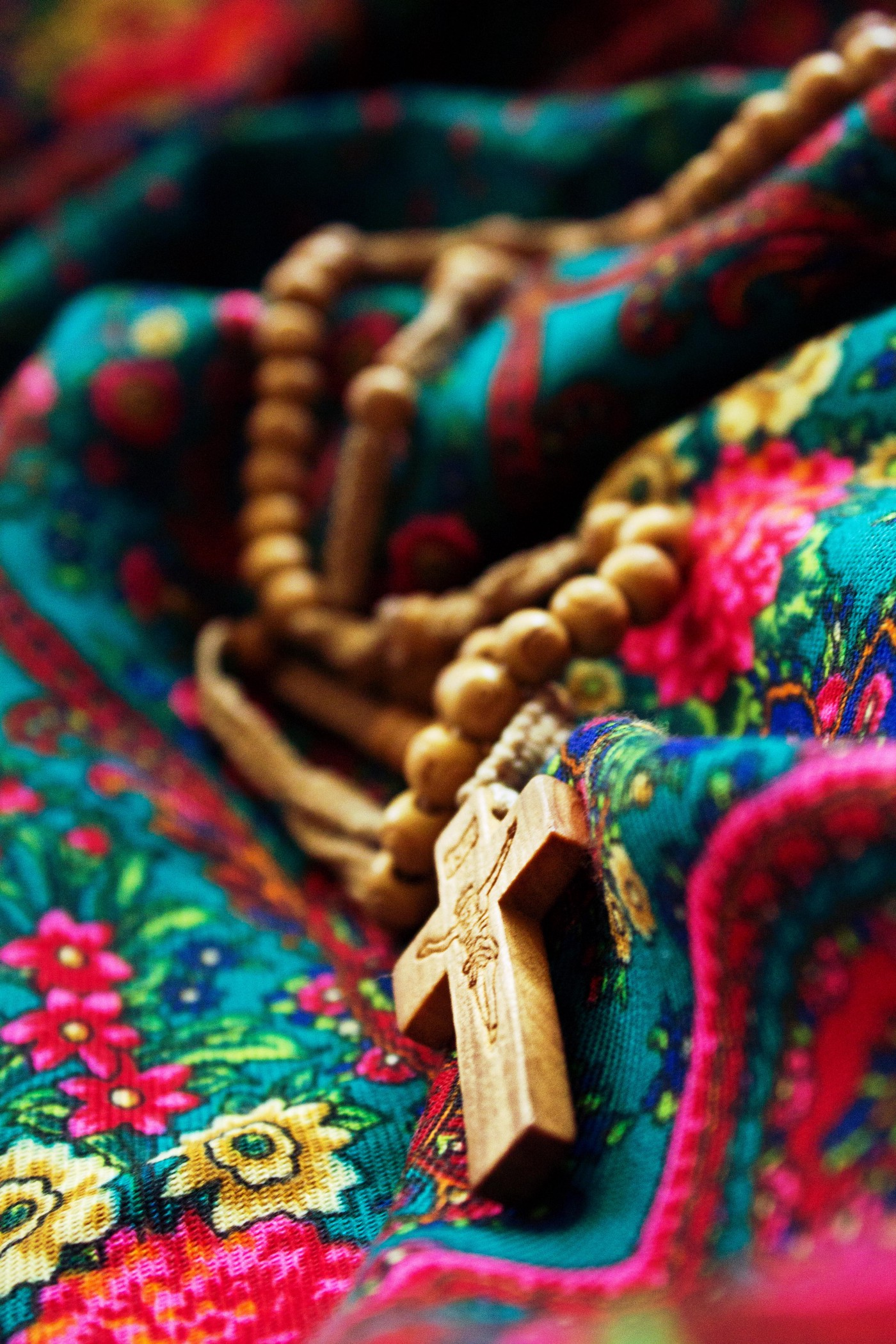 A rosary laying on a colorful cloth